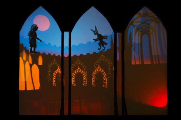 Alice and the White Rabbit run across a wall in this shadow theatre production