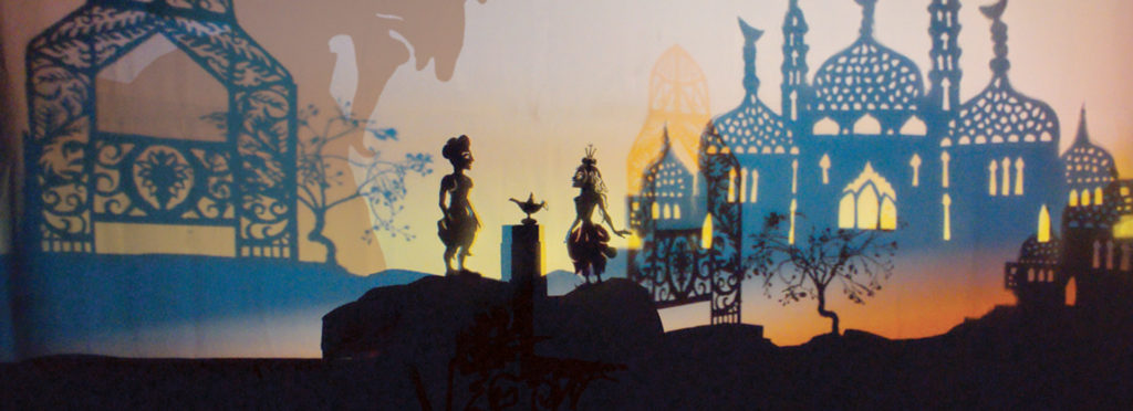 A shadow puppet scene from Aladdin with the grand palace in the background and two shadow puppets standing either side of the magic lamp