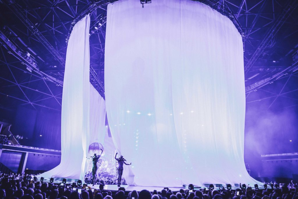 Large curtains on stage at the SSE Hydro Glasgow with emerging dancers holding umbrellas