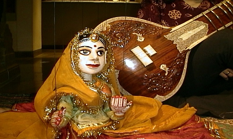 The marionette Saraswati sits in front of a sitar