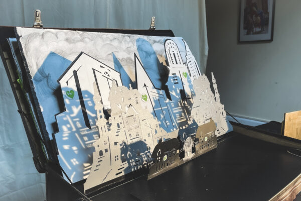 Suitcase scenery unfolded to reveal a cityscape full of buildings and houses